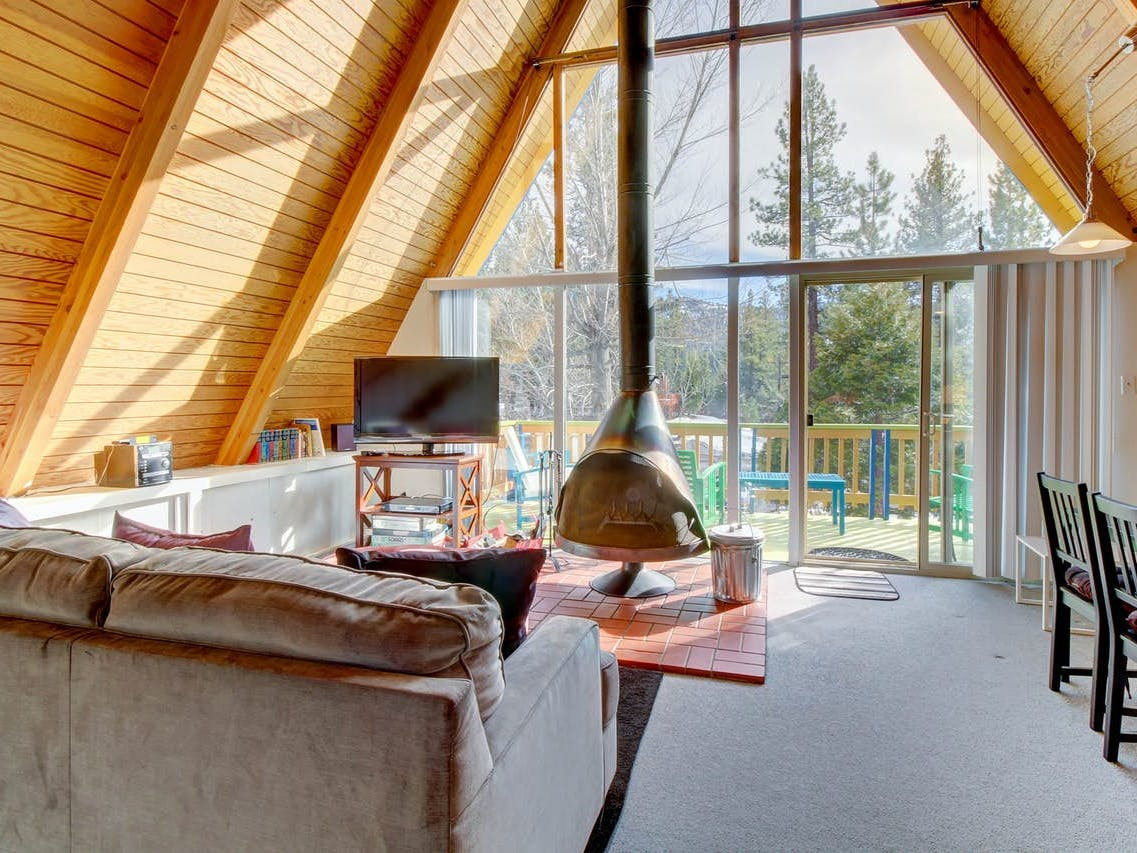 Big Bear Lake, CA a-frame vacation rental featuring floor-to-ceiling windows and a wood-burning fireplace