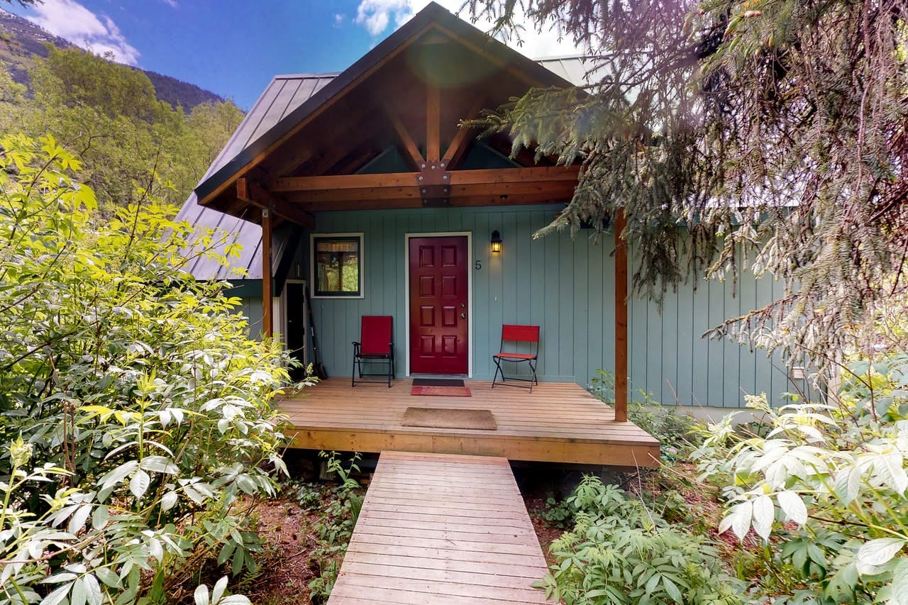 a girdwood cabin with a red door and red chairs on the front porch