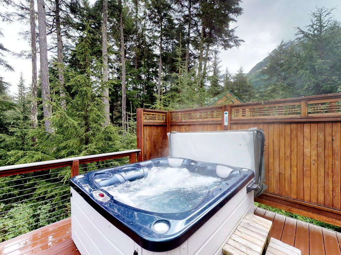 a bubbling hot tub on a deck with the forest in the backdrop