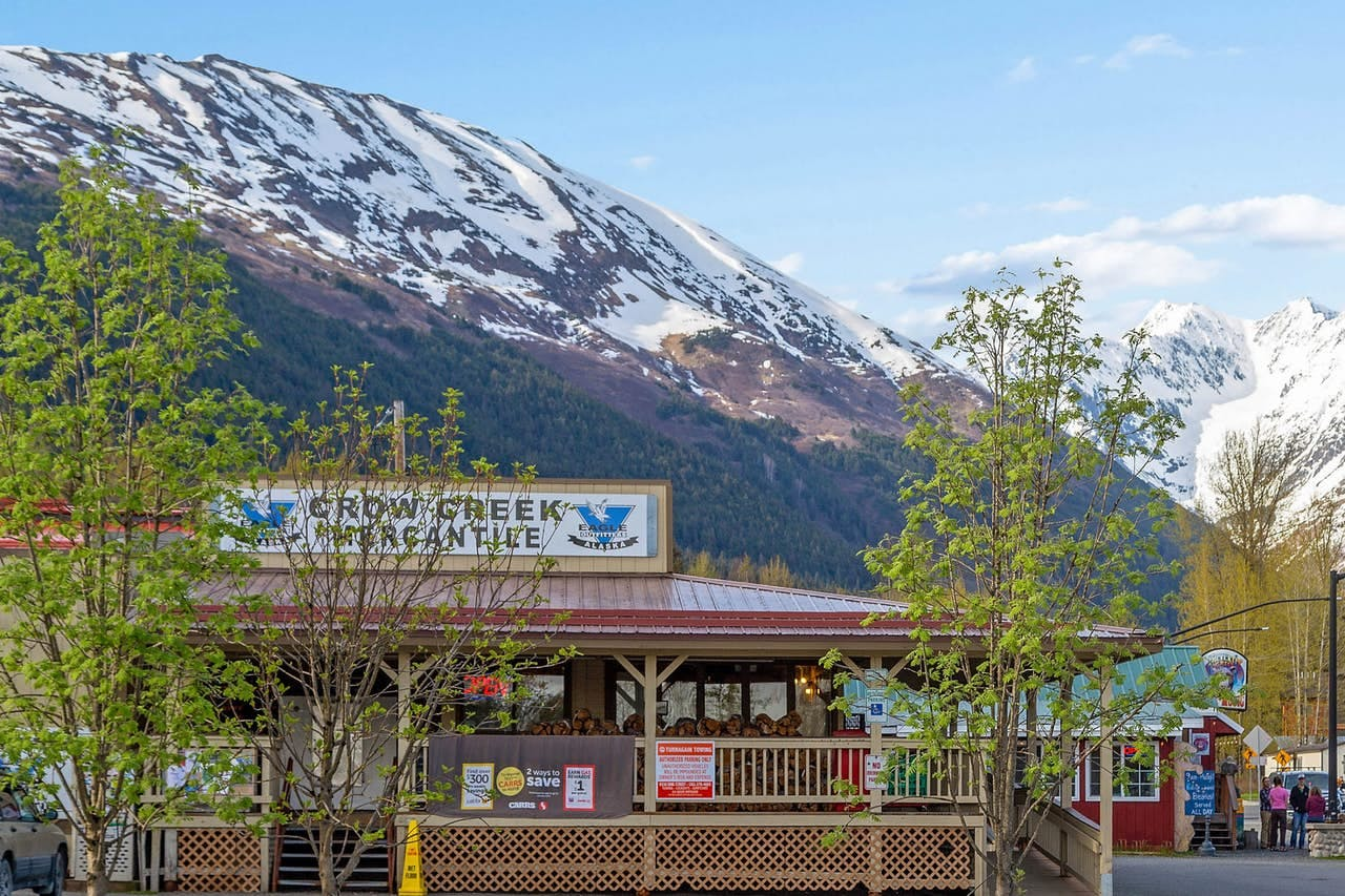 a local shop in girdwood alaska, with a snowy mountain behind it