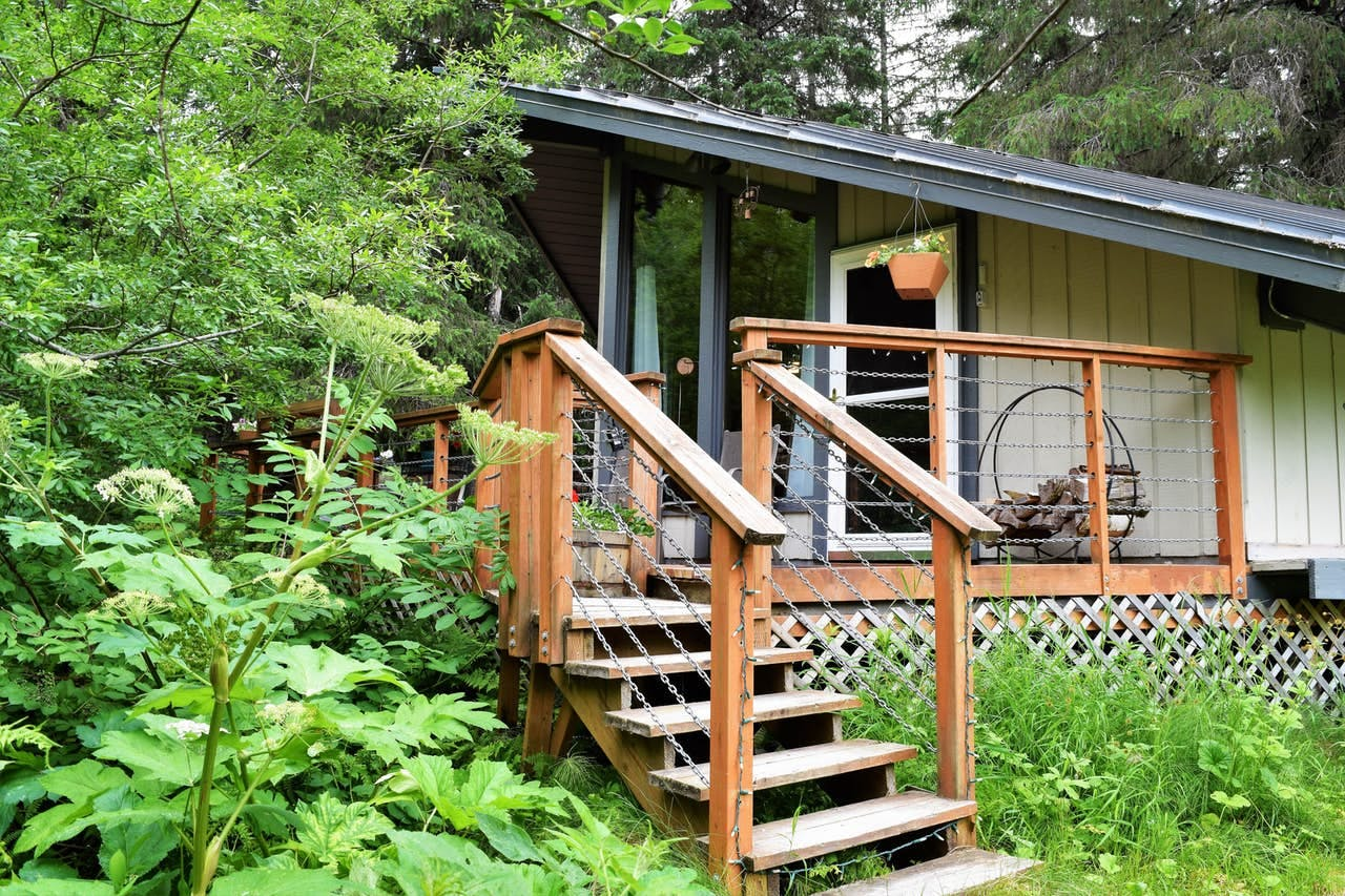 the front porch leading up to a small cabin in girdwood, alaska