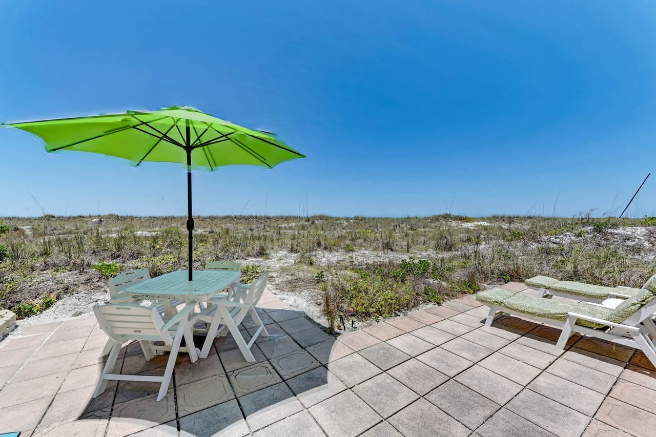 a patio with a table and beach chairs overlooking the sand dunes