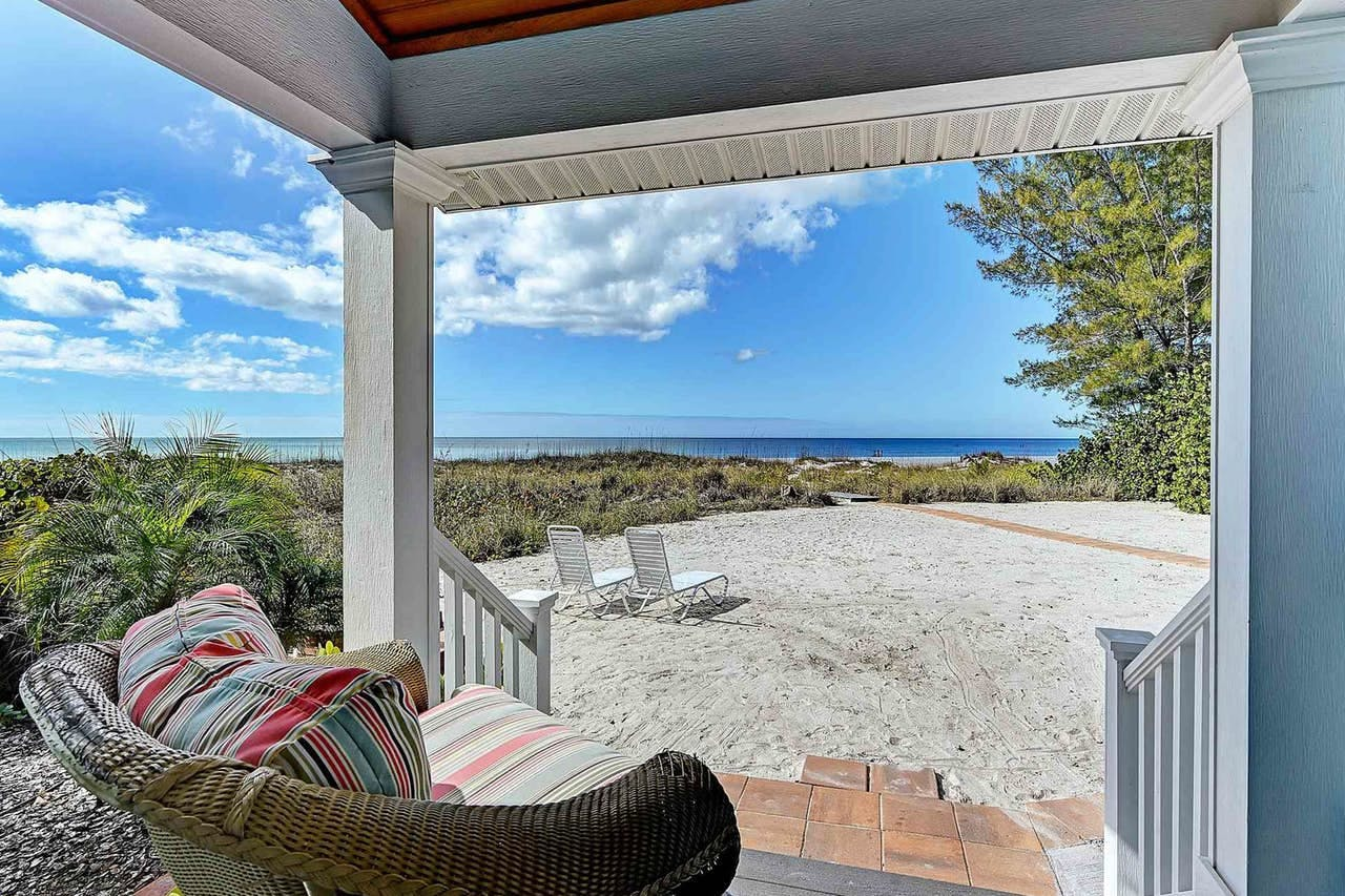 a porch overlooking a sandy backyard and path to the beach in Anna Maria