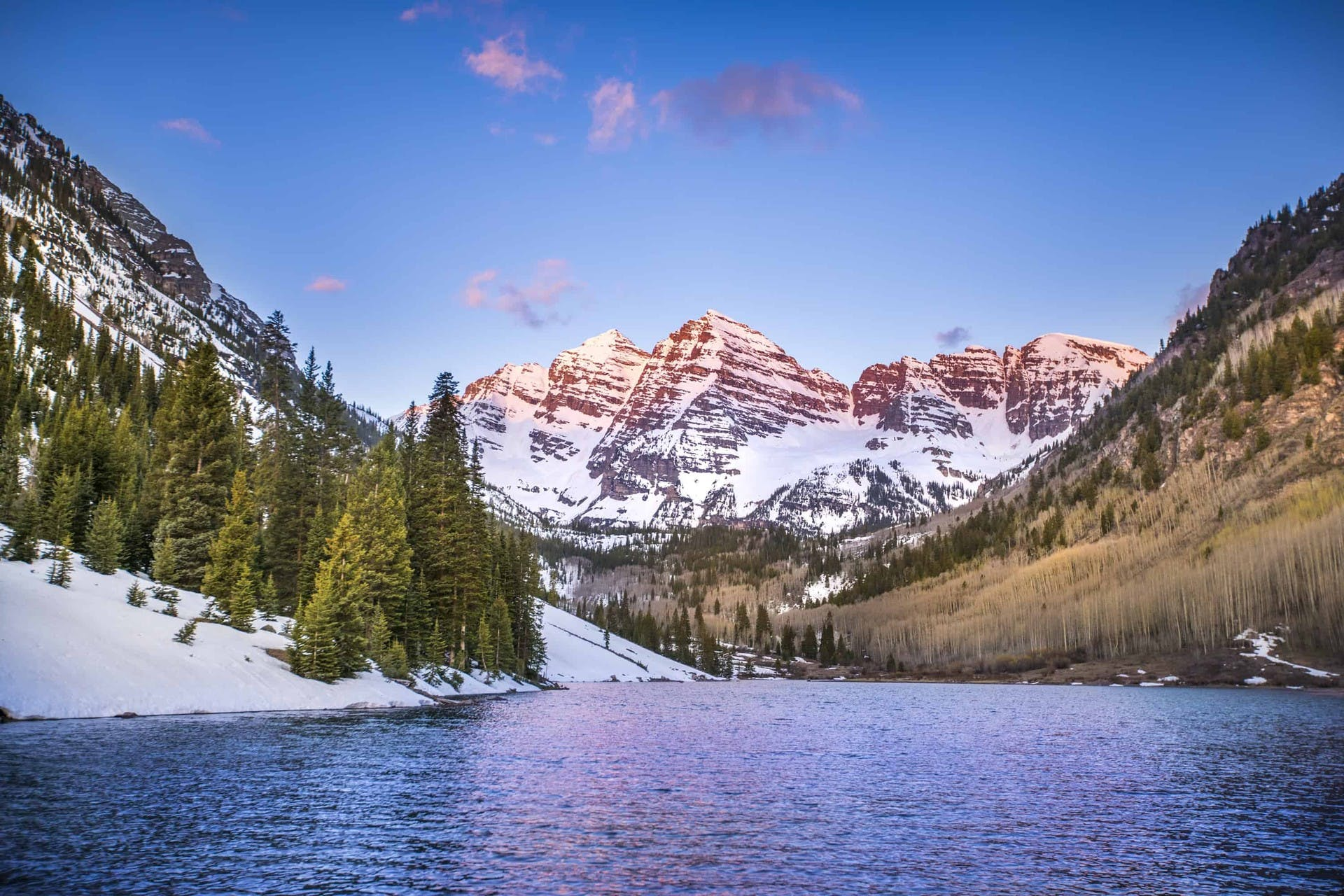 Lake in Colorado surrounded by snowy mountain peaks