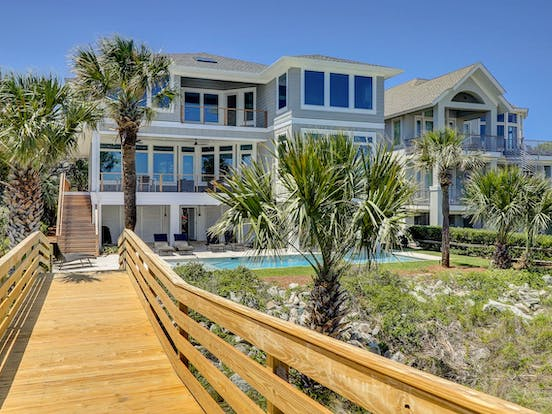Backyard of Hilton Head beach house with pool, palm trees and a boardwalk