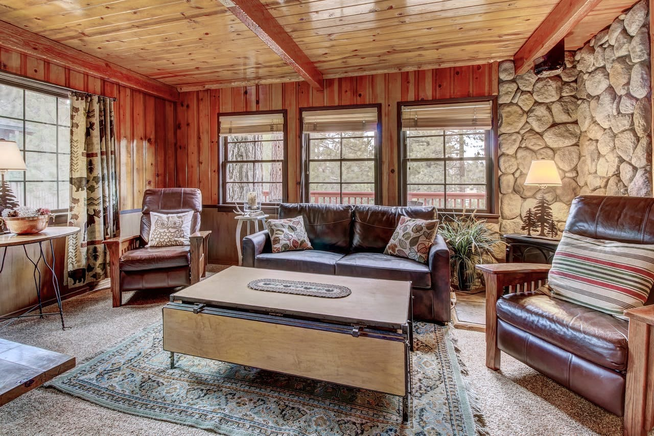 Wood paneling and stone walls create a warm, rustic vibe in this Big Bear vacation rental