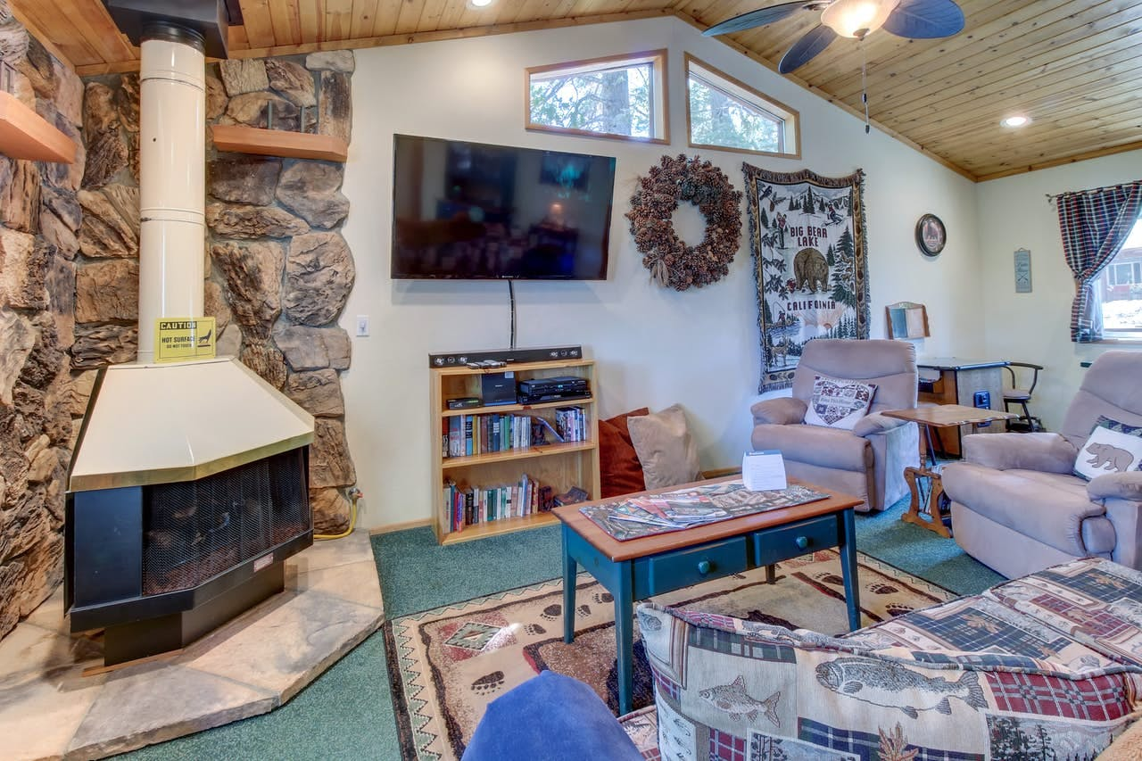 Gas fireplace in the living room with slanted wood ceiling of Big Bear, CA vacation rental