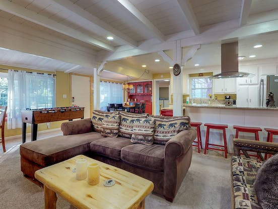 Living room of Big Bear Lake, CA vacation rental with ample seating, foosball table, dining area and breakfast bar