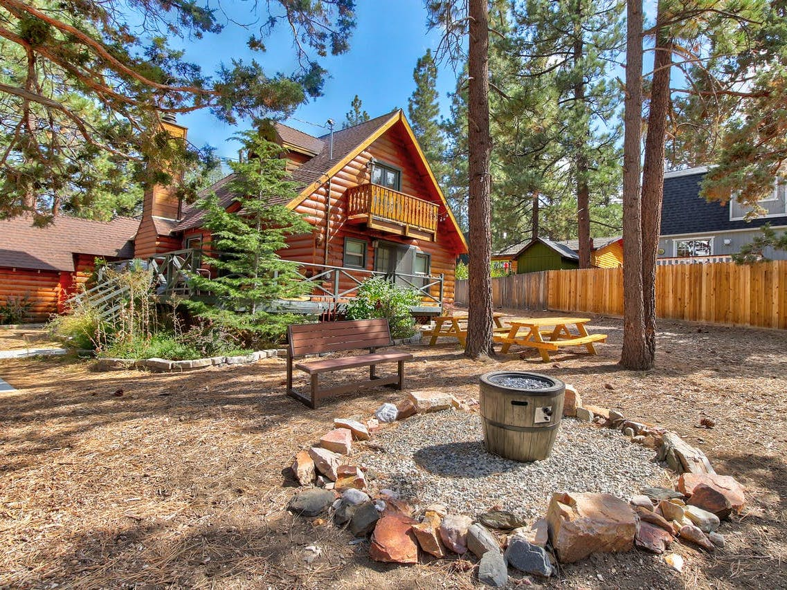 Fenced backyard suitable for dogs and large groups with picnic tables and firepit located in Big Bear City, CA