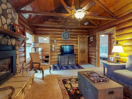 Wood beams, stone walls and a warm fireplace in vacation rental located in Big Bear City, CA