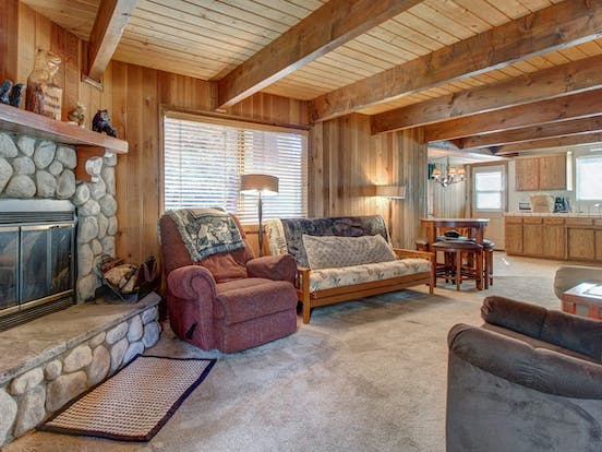 Living area of vacation rental in Big Bear, CA with wood beams, warm couches and a wood-burning fireplace