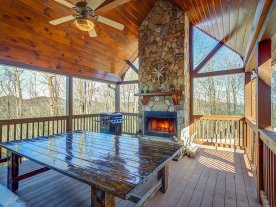 Outdoor covered deck with fireplace, grill and tons of seating located in Blue Ridge Mountains