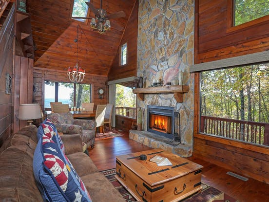 Living area of vacation cabin showcasing tons of windows and a huge stone fireplace located in the Blue Ridge Mountains