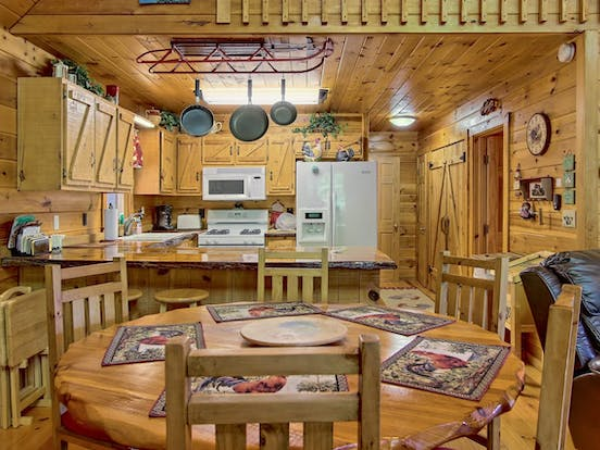 Kitchen area of vacation rental featuring counter-top seating, dining table, and mountain decor