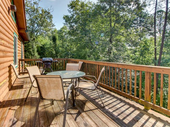 Outdoor deck with grill and plenty of seating located of vacation cabin in the Blue Ridge Mountains