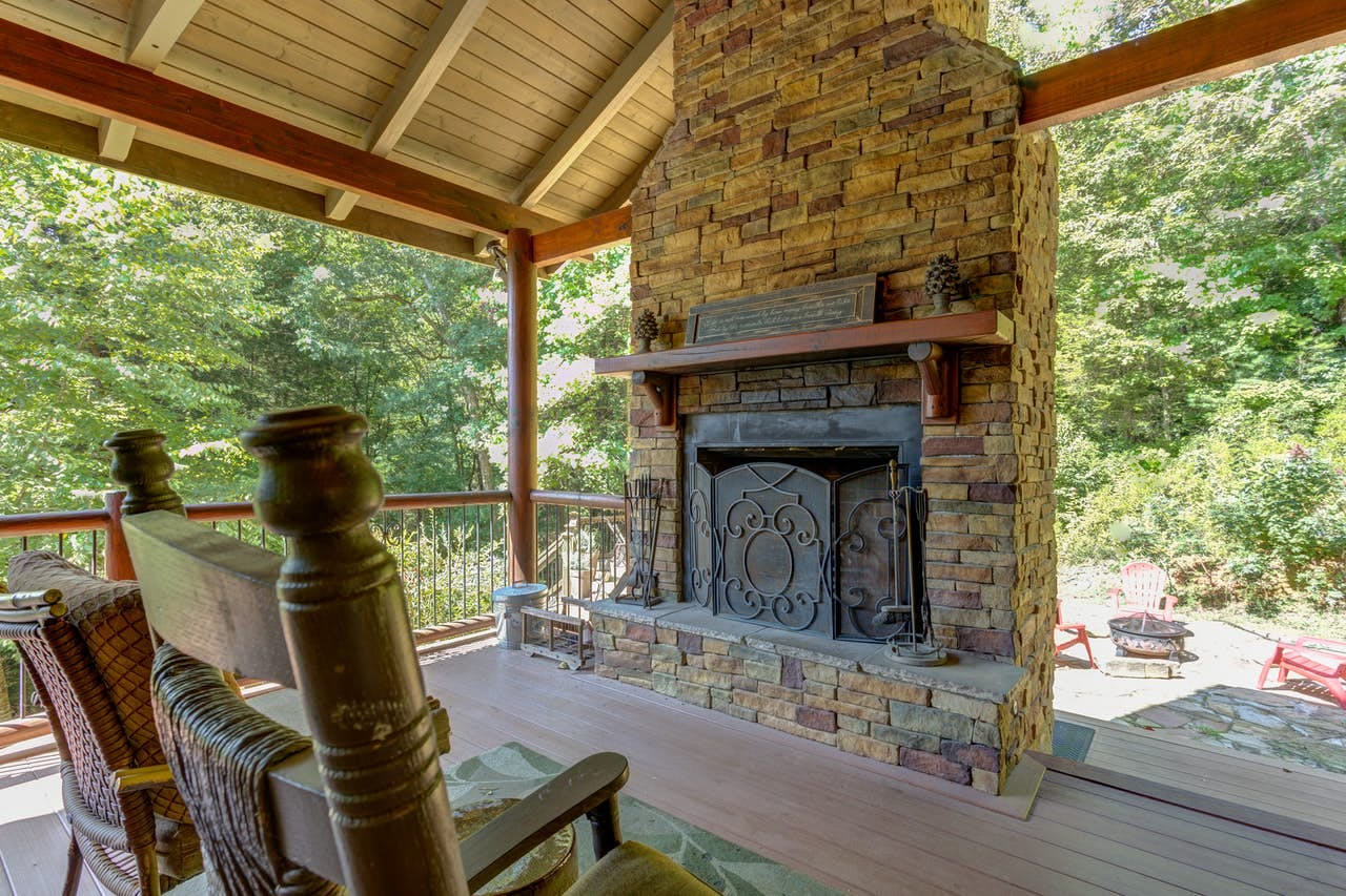 View of firepit from covered deck with outdoor fireplace located in North Georgia