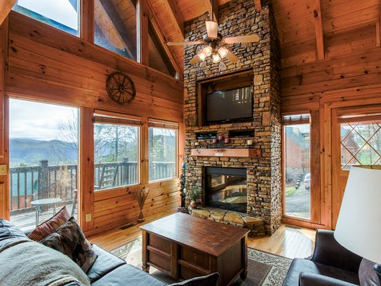 Living area of Blue Ridge Mountains cabin rental featuring stone fireplace, deck and ample seating