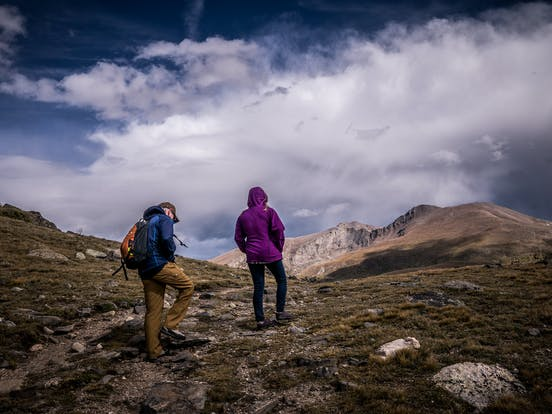 two hikers making their way up to a peak in colorado