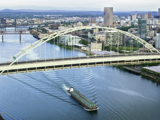 willamette river with boat and bridge in portland, oregon