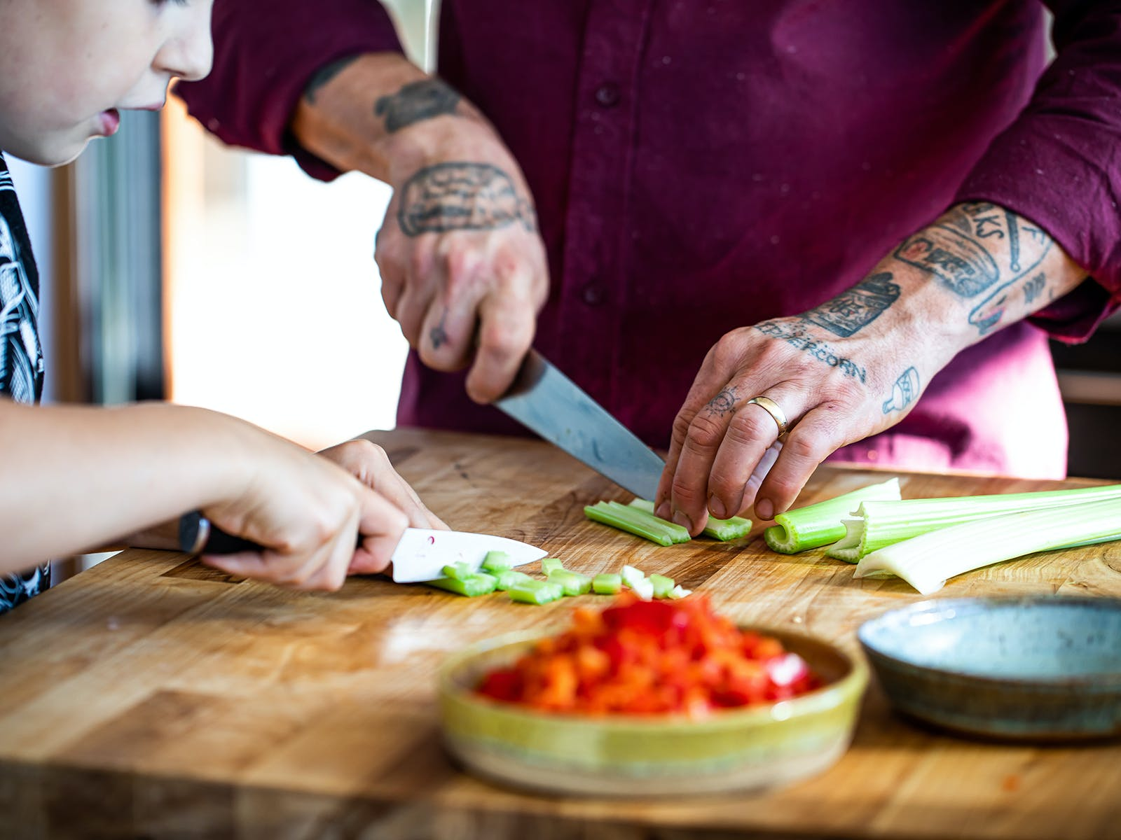 chef gabriel chopping vegetables with his son