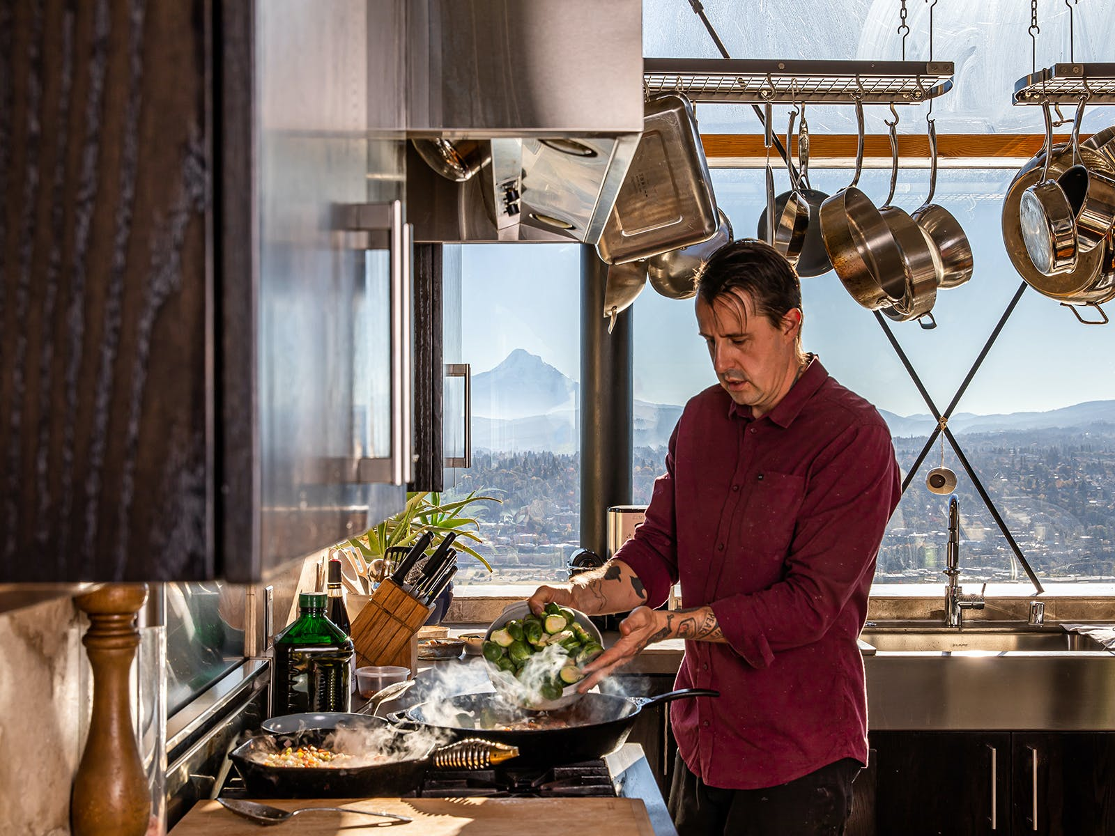 chef gabriel cooks brussels in a cast iron pot on the stove with mount hood in the distance