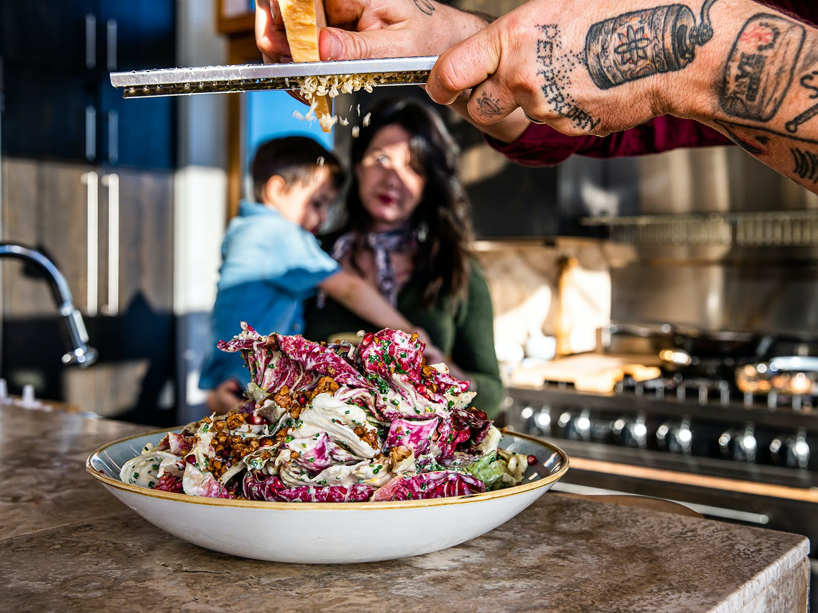 chef gabriel grates cheese over his radicchio salad
