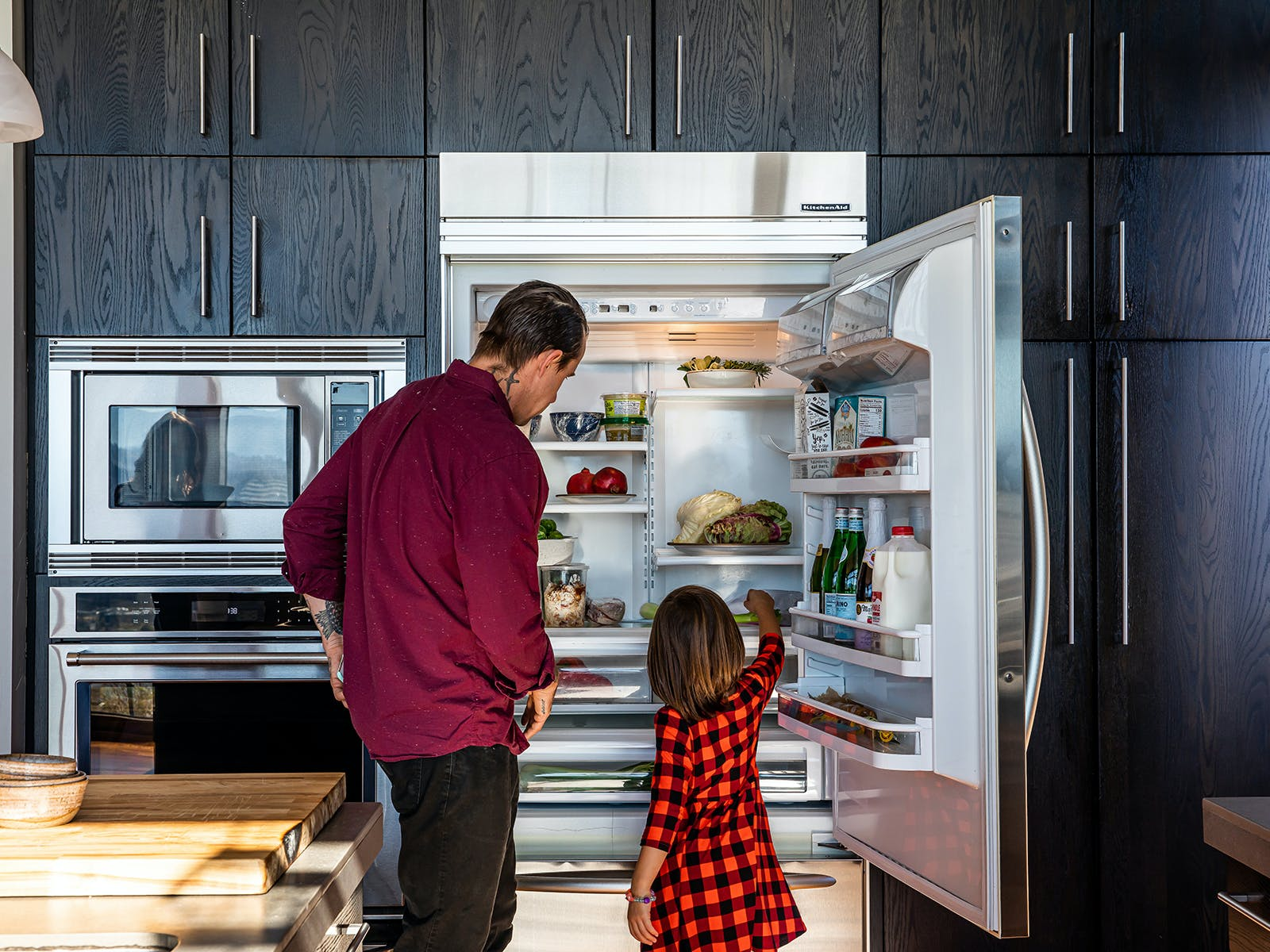 chef gabriel and his daughter take stock of the fridge of their vacation rental