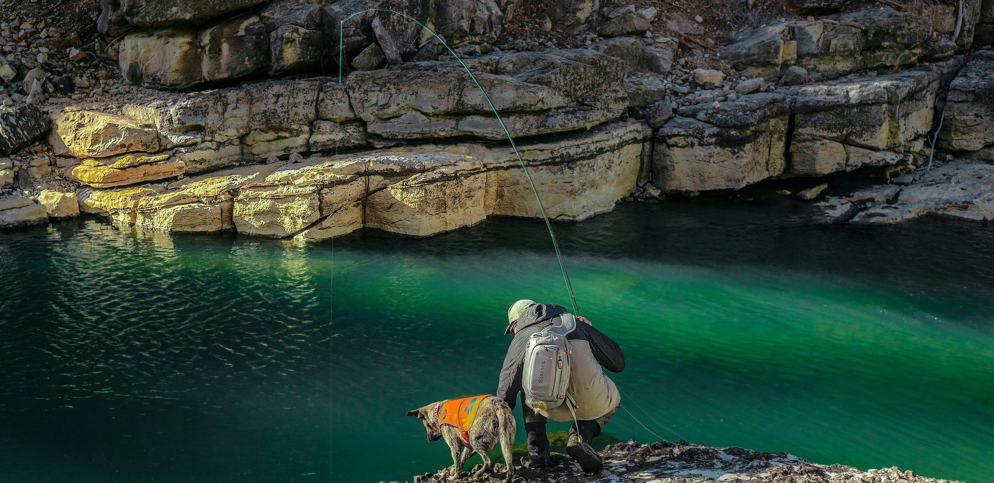 A fisherman and his dog near Piedra River Hot Springs in Colorado