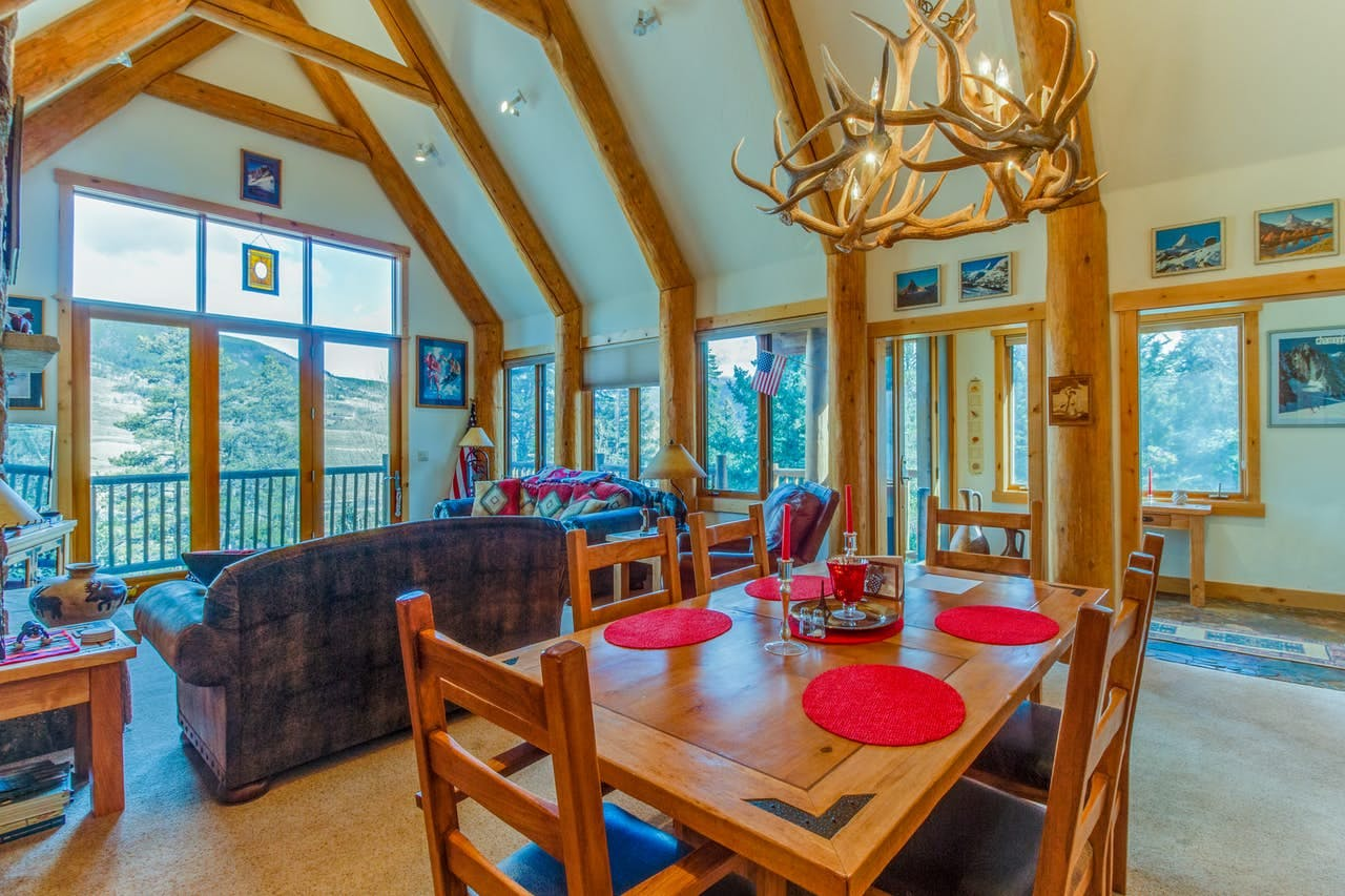 Interior of Treehouse Townhome vacation rental featuring an amazing antler chandelier, walls of windows and cozy couches