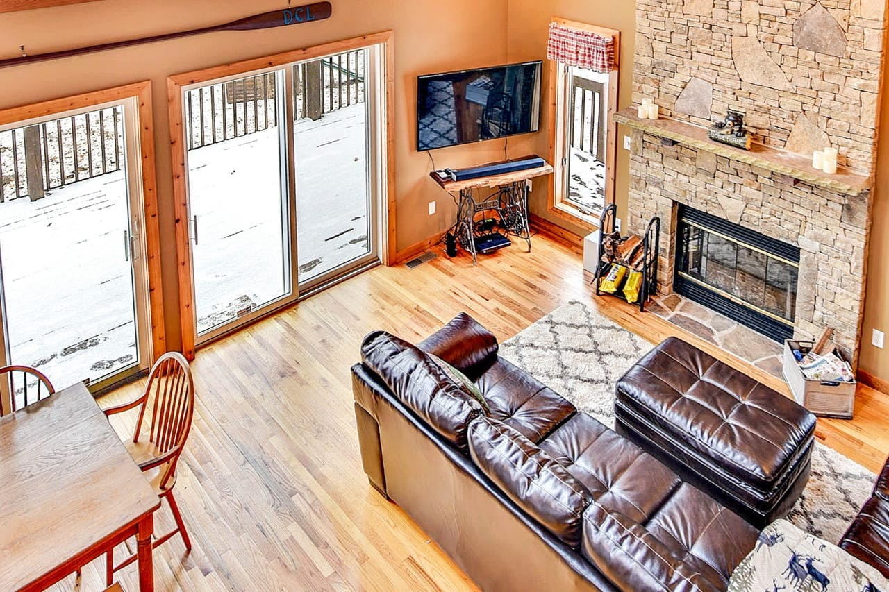 View of downstairs with large fireplace, leather couches and dining area
