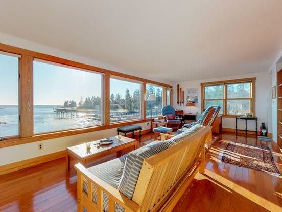 Sunroom of Boothbay Harbor vacation rental with generous views of Cape Harbor, Cape Island, and the Atlantic Ocean