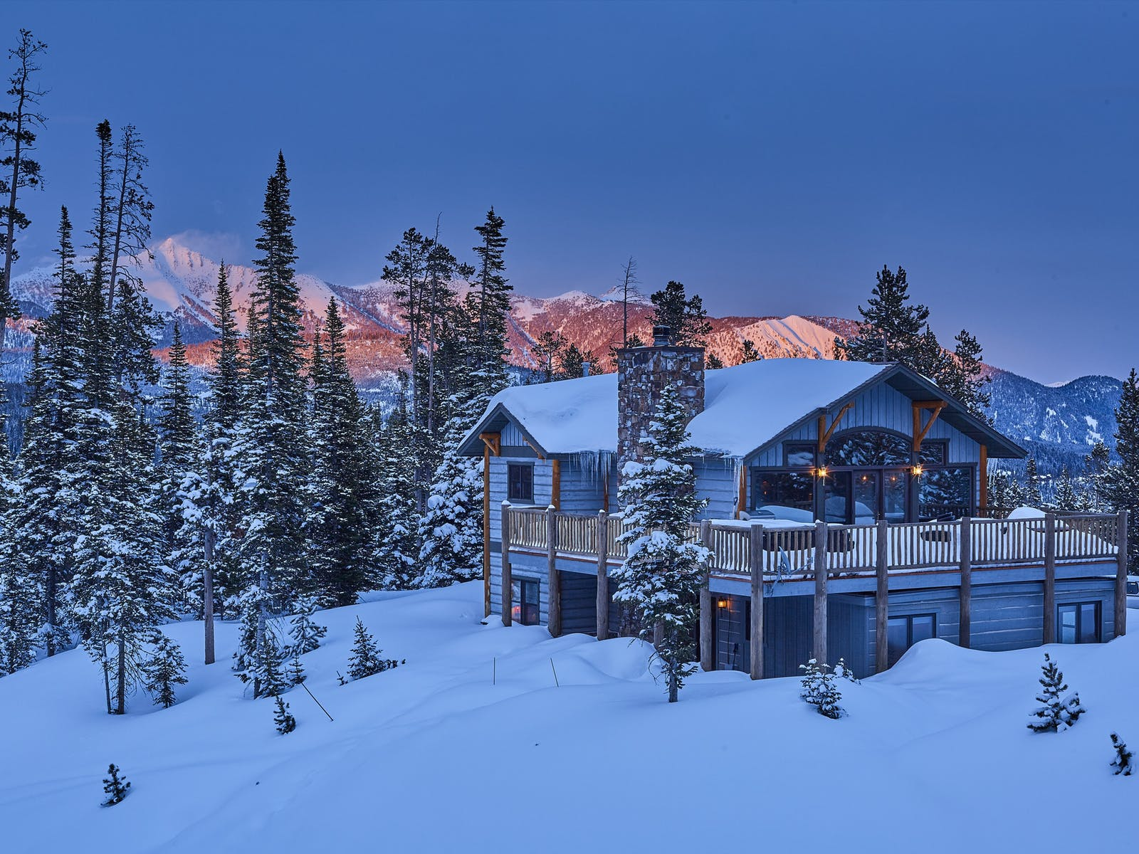 Beautiful view of Big Sky, MT vacation home surrounded by snowy pines and mountains