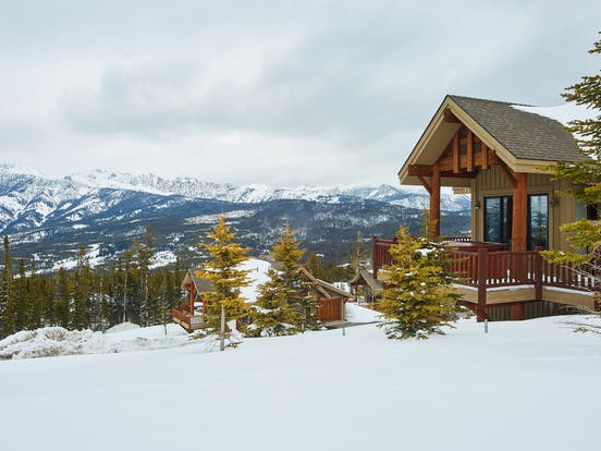 A cabin on a snowy mountainside in Big Sky, Montana