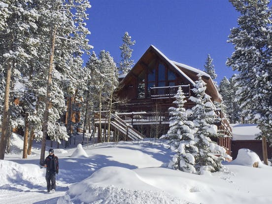 man poses in the snow in front of his breckenridge, co cabin rental