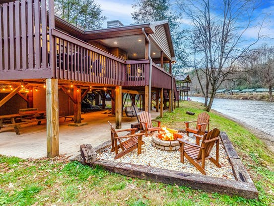 fire in a firepit near a river outside a smoky mountains vacation rental