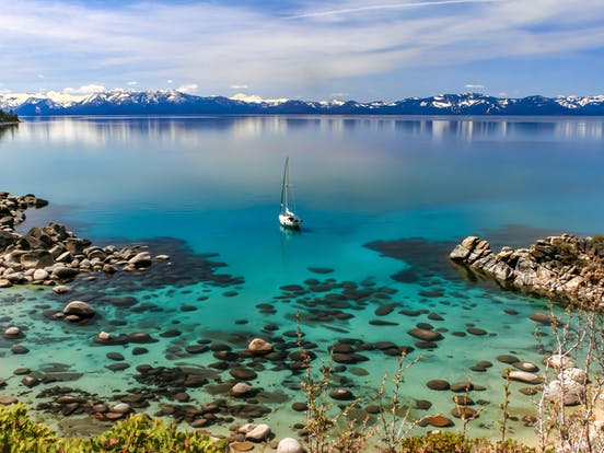 Lake Tahoe surrounded by snow-covered mountains with sailboat and crystal clear waters