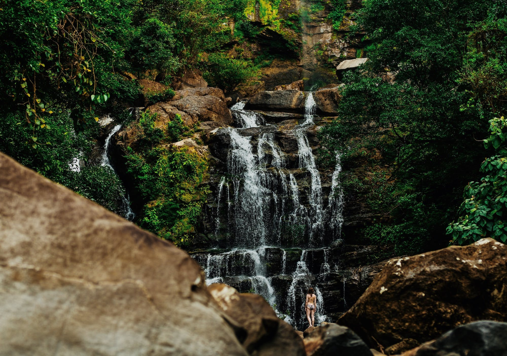 Woman at the bottom of a waterfall surrounded by greenery