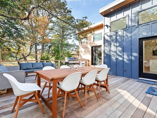 Fully furnished deck with cozy furniture, a gas grill and views of Seaview, NY
