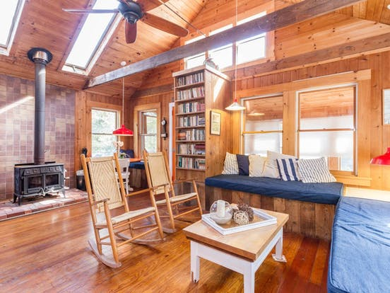 Wood burning fireplace, wood interior and dual rocking chairs inside this Fire Island vacation rental