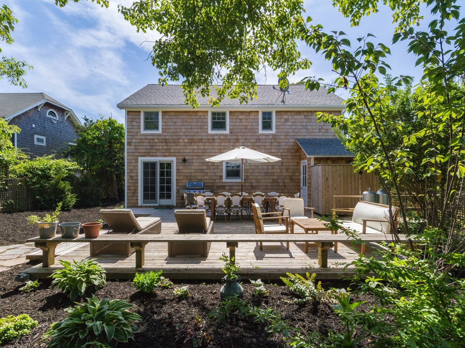 View of backyard, back deck and outdoor dining space of Fire Island vacation rental