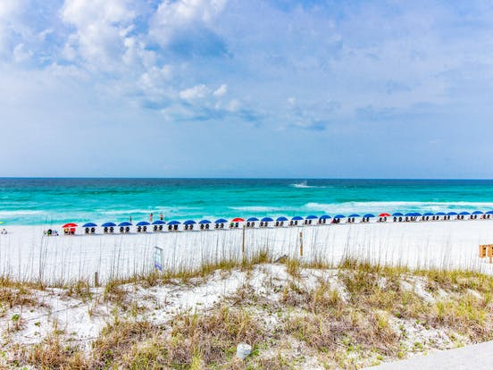 Beach with lounge chairs in Seaside, FL