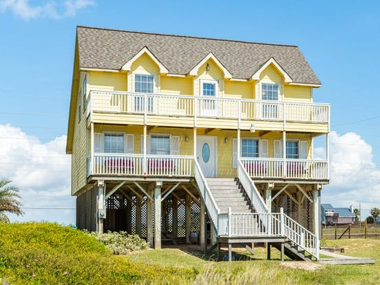 Yellow two-story beach house rental located in Galveston, TX