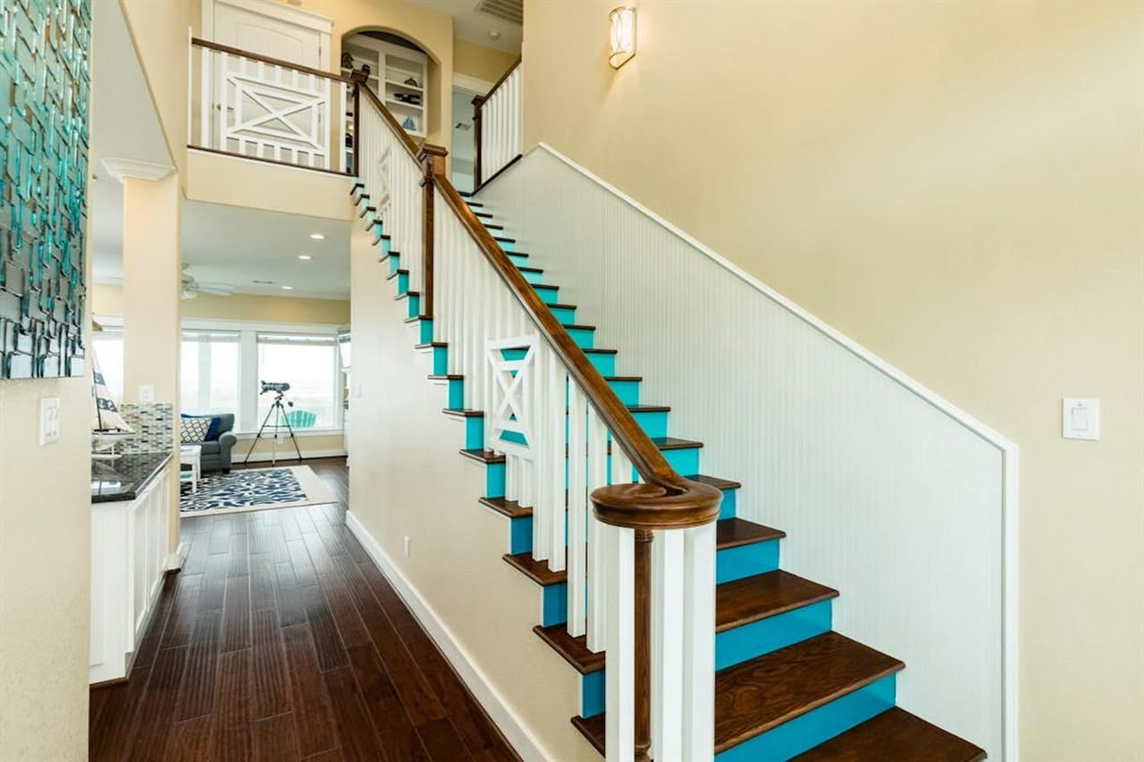 Bright blue-green stairs inside vacation home located in Galveston
