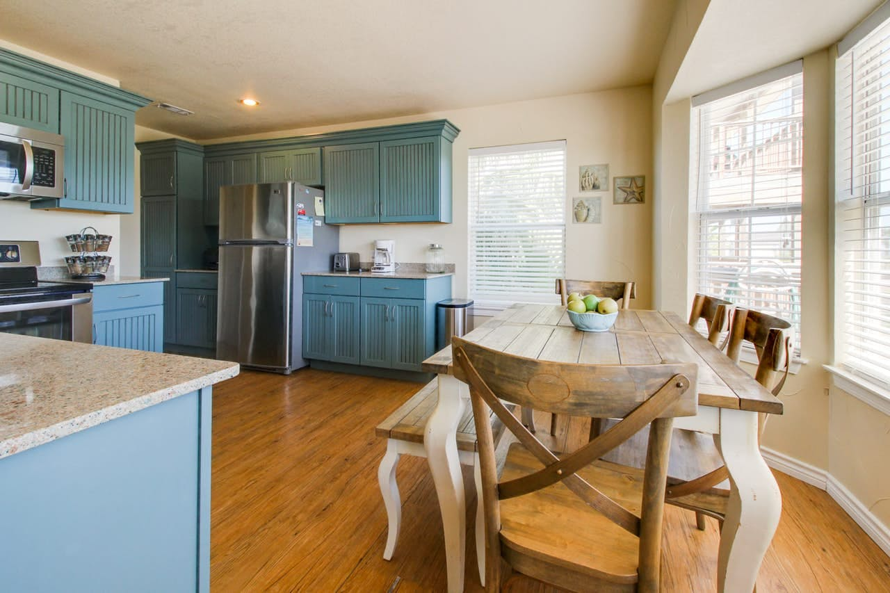 kitchen and dining area with blue cabinets and wood floors of Galveston beach house