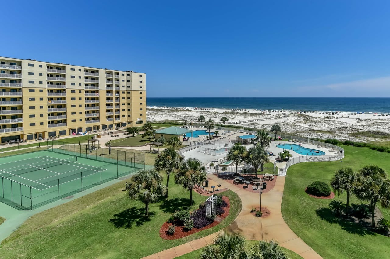 a tennis court and pools, near the beach at a Gulf Shores Resort