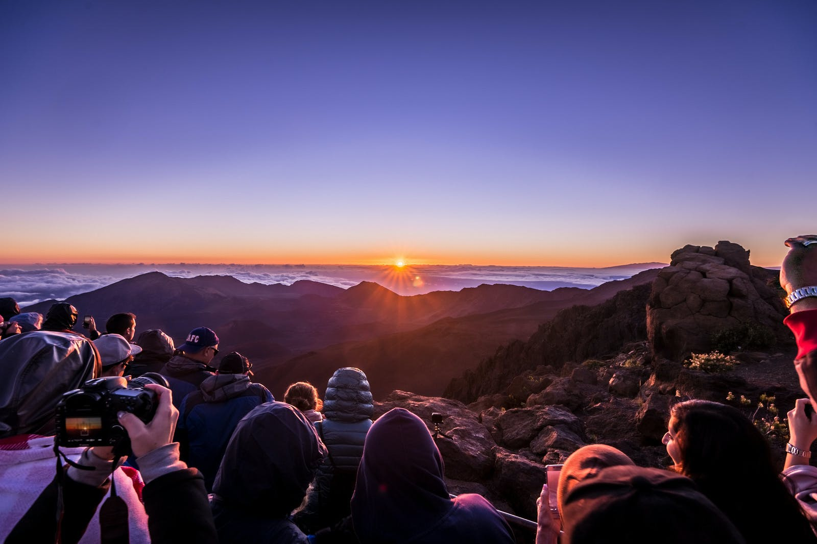 a group of people seeing the sun rise at haleakala