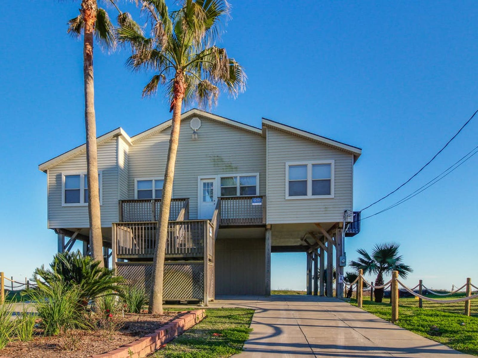 Galveston, TX vacation home with palm trees and blue skies