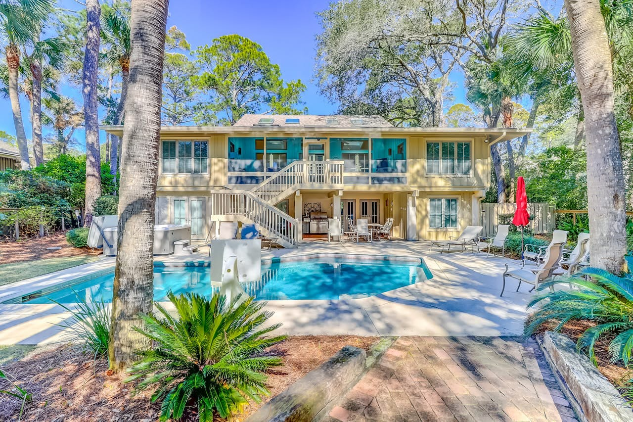 resort-style pool with hot tub sits outside a luxury vacation rental in Hilton Head
