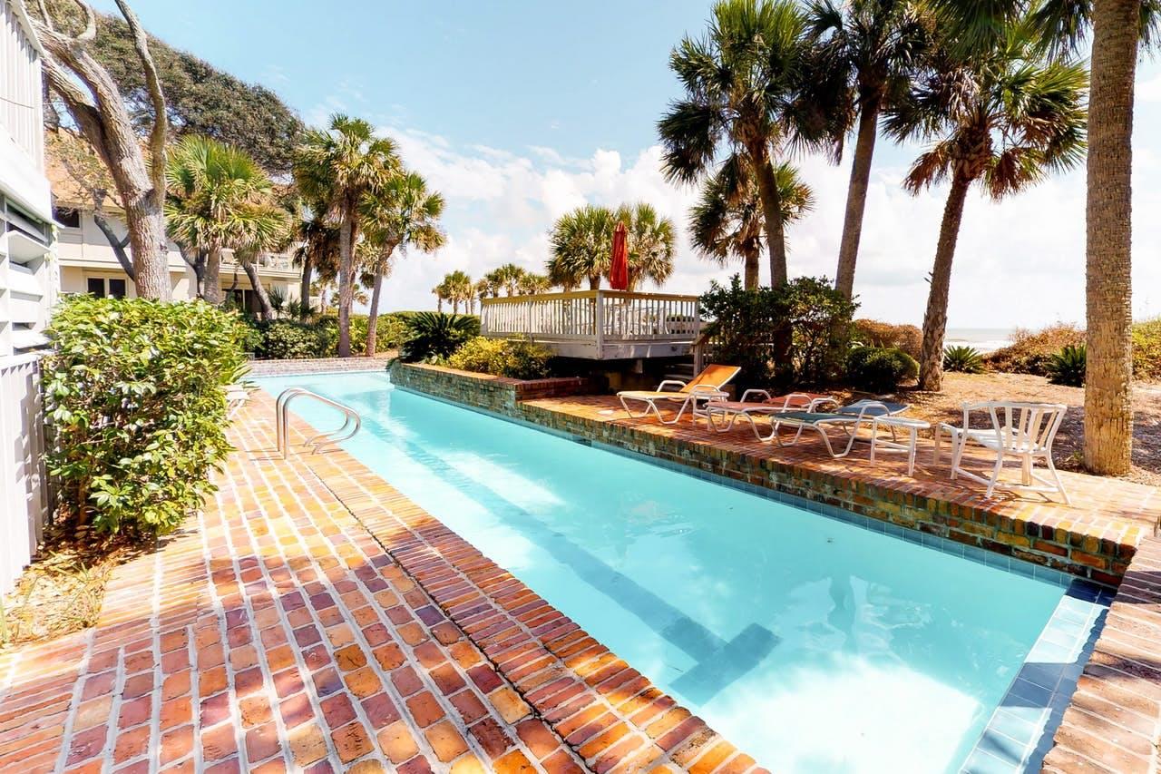 View of private outdoor lap pool, lounge chairs and nearby beach access