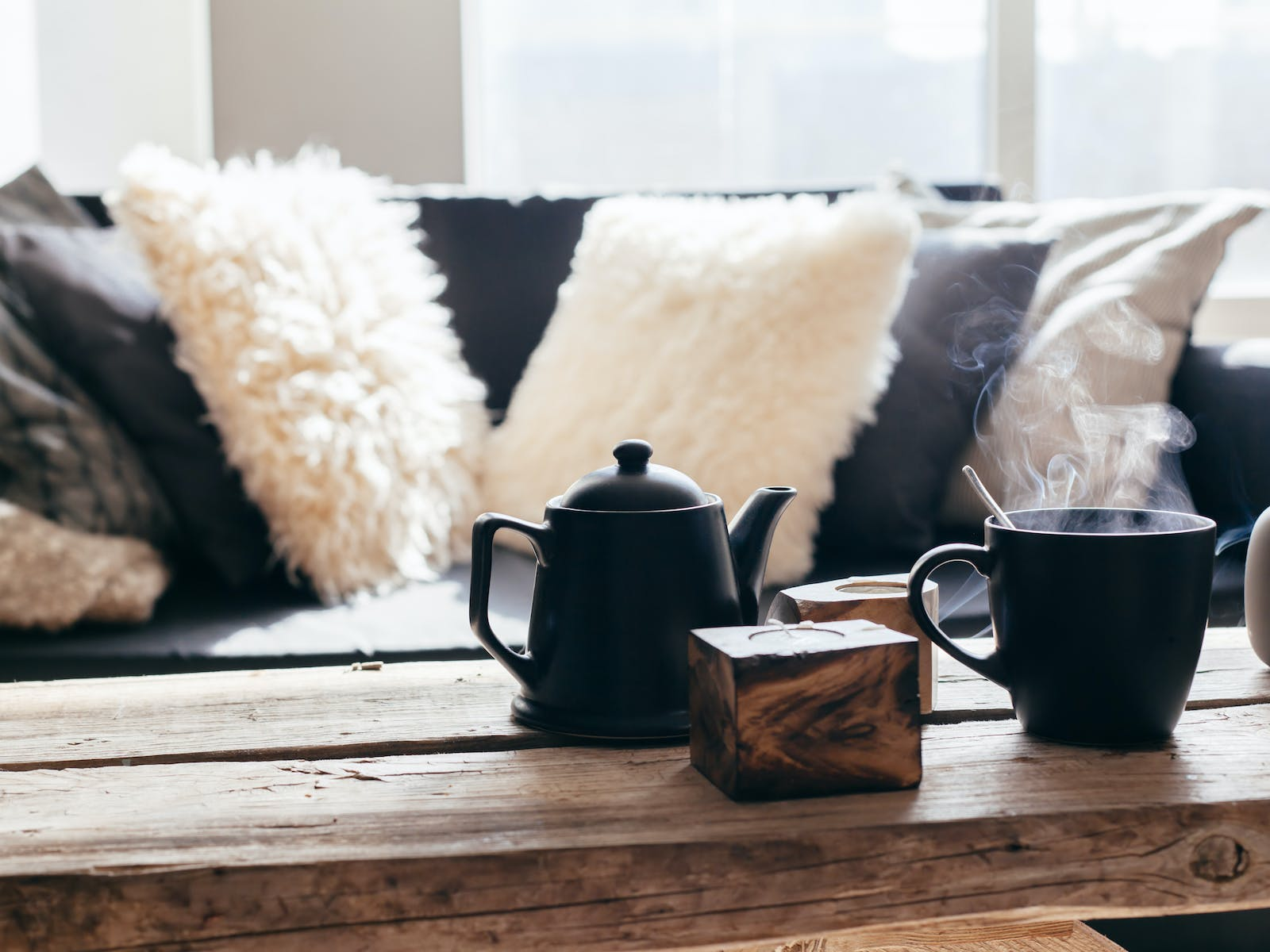 A hot cup of tea sits on coffee table inside vacation rental